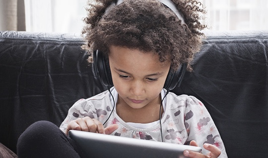 A child wearing headphones, using an iPad