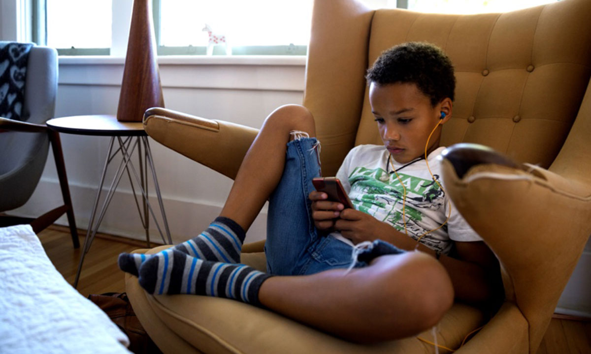 Boy relaxes on a chair wearing headphones and playing on his phone