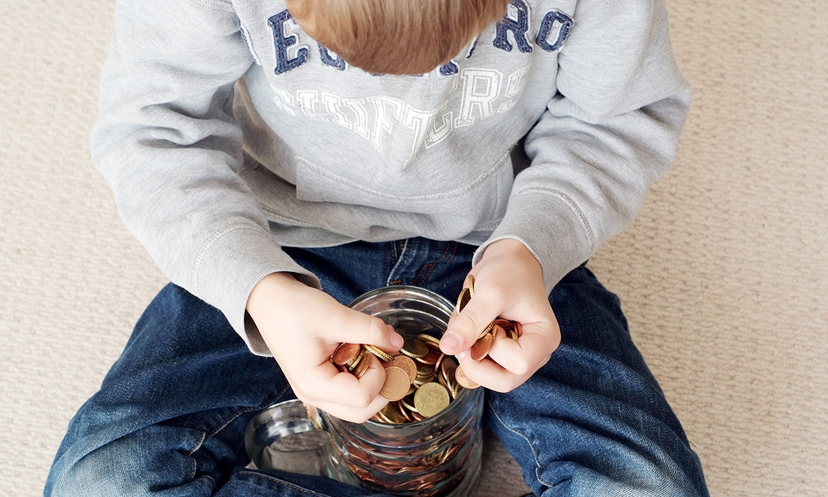 Young boy counts money from a savings jar