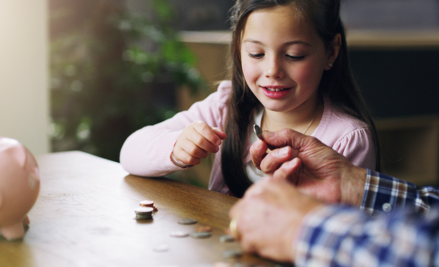 Young girl counts her coins on a table