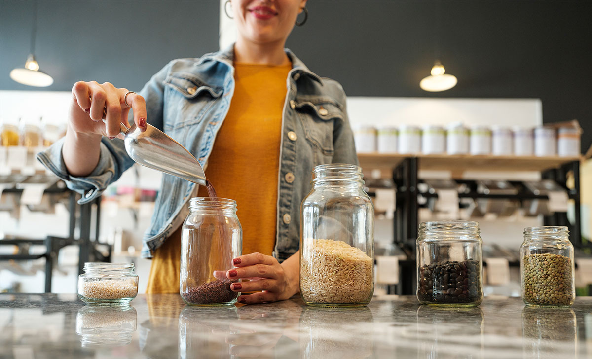 A girl fills reusable glass jars with grains and pulses