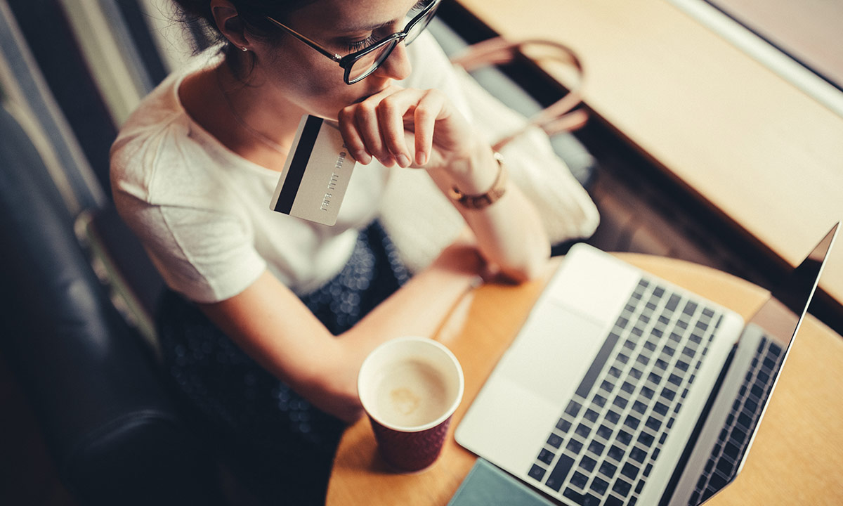 A young lady sits in a coffee shop with her laptop and holds her bank card in her hand